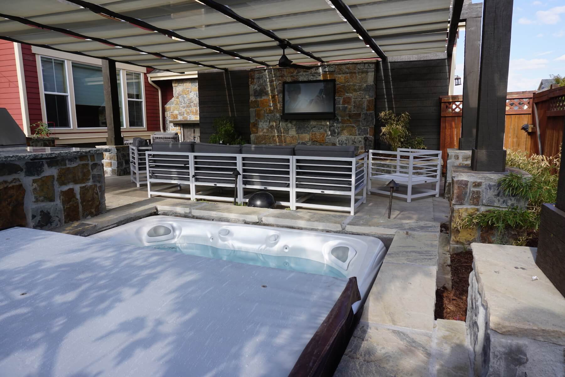 Hot tub with pergola outdoor kitchen paver patio fireplace hot tub lowry co